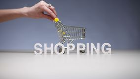 Woman with market trolley on background word shopping on sale and discounts. Woman with market trolley on background word shopping. Shopping on sale and stock footage