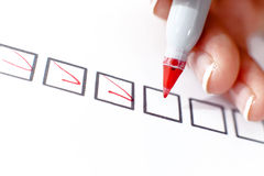 Woman marking in a checkbox. A woman selects and marks in the top box of a series Royalty Free Stock Images