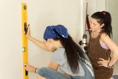 Woman marking a vertical line on a wall stock photo