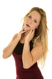 Woman in maroon dress hands by face close stock photo