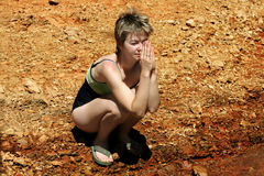 Woman from Mars. Young woman praying in a desert Royalty Free Stock Photography