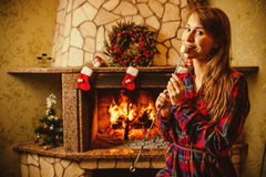 Woman with marshmallow by the fireplace. Young woman smiling and Royalty Free Stock Images