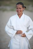 Woman in martial art. Portrait of beautiful smiling tanned woman in kimono outside stock photography