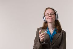 Woman with martini-01. A young business woman relaxes with a martini and music after work Stock Photo