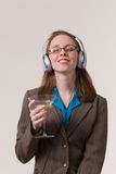 Woman with martini-02. A young business woman relaxes with a martini and music after work Royalty Free Stock Image