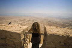 Woman Masada. A woman, flanked by a grackle, looks toward the Dead Sea from the ancient hilltop fortress of Masada in Israel Royalty Free Stock Photo