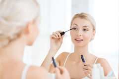 Woman with mascara applying make up at bathroom Stock Photo