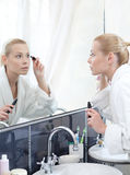 Woman mascaras her eyelashes Royalty Free Stock Photo