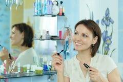 Woman mascaras her eyelashes Stock Image