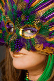 Woman in Mask. A portrait of a beautiful woman in a brightly colored feather mask Stock Image
