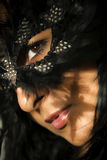 Woman in mask. A portrait of a beautiful asian woman wearing a feather mask and staring up towards a crucifix Stock Images