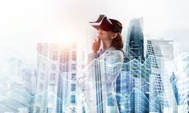 Woman in mask against sunrise above city trying virtual reality stock images