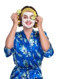 Woman with a mask. Beautiful young woman with a mask and cucumber slices on her face on a white background stock image
