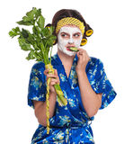 Woman with a mask. Beautiful young woman with a mask eats cucumber slice isolated over white royalty free stock image