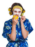 Woman with a mask. Beautiful young woman with a mask on her face eats apple isolated over white stock photography