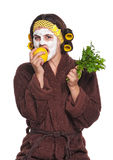 Woman with a mask. Beautiful young woman with a mask on her face eats apple isolated over white royalty free stock photos
