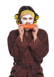 Woman with a mask. Beautiful young woman with a mask on her face eats carrot isolated over white royalty free stock photos