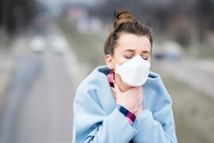Woman with mask in the city. Young woman in protective mask feeling bad in the city with air pollution. Smog concept stock images