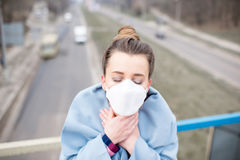 Woman with mask in the city. Young woman in protective mask feeling bad in the city with air pollution. Smog concept stock photo