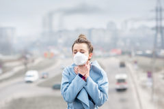 Woman with mask in the city. Young woman in protective mask feeling bad in the city with air pollution from traffic and manufacturing. Smog concept royalty free stock photos