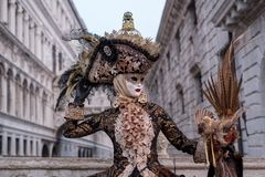 Woman in mask and costume with birdcage, Bridge of Sighs in the background, during the Venice Carnival