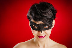 Woman in mask looks seductively Royalty Free Stock Image