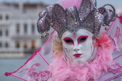 Woman in mask and ornate pink jester`s costume at Venice Carnival Carnivale di Venezia stock image