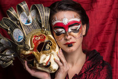 Woman with mask. Portrait of beautiful young girl with creative make up and big carnival mask in her hands, brunette hairstyle. Louis court intrigues. Red Stock Photography