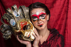 Woman with mask. Portrait of beautiful young girl with creative make up and big carnival mask in her hands, brunette hairstyle. Louis court intrigues. Red Royalty Free Stock Photos