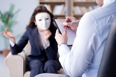 The woman with mask during psychologist visit. Woman with mask during psychologist visit Royalty Free Stock Images