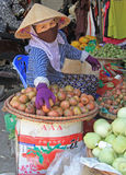 Woman in mask is selling fruits and vegetables on street market in Vinh, Vietnam Stock Photography