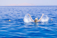 Woman with mask snorkeling in clear water waving Stock Photo
