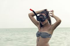 Woman with a mask for snorkeling before diving. Woman with a mask for snorkeling position belt tension before sea diving stock photo