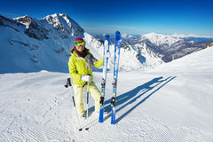 Woman in mask standing and holding ski alone. Woman in mask standing and holding ski and ski poles during sunny winter day on Krasnaya polyana ski resort and Royalty Free Stock Photos