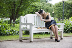 Woman  with mask take rest on bench Stock Photo