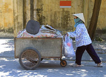 Woman in mask is transporting a cart with clothes Royalty Free Stock Photos