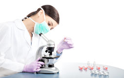 Woman in mask using pipette and microscope. Stock Image