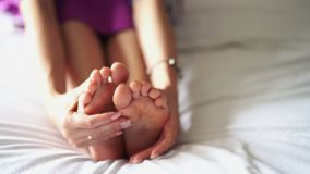 A woman massaga the bottom of his tired, sore foot. stock footage