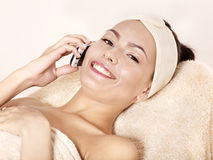 Woman on massage table call by phone. Stock Photography