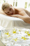 Woman On Massage Table With Flowers In Foreground Royalty Free Stock Photography