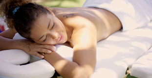Woman on massage table at outdoor spa Royalty Free Stock Images