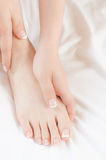 Woman gently massages her own pedicured foot Stock Photography