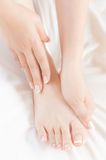 Woman gently massages her own pedicured foot Royalty Free Stock Photography