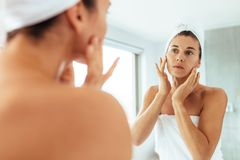 Woman taking care of her body after bath. Woman massaging her face looking at a mirror in bathroom. Woman in towels wrapped around head and body after bath royalty free stock photos