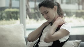 Woman massaging her neck and shoulder from an ache or pain