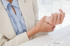 Woman massaging her sore wrist. In her office Royalty Free Stock Photo