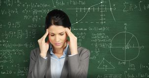Woman massaging her temples in front of chalkboard with moving math calculations
