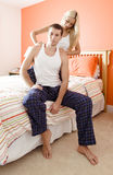 Woman Massaging Man's Shoulders in Bedroom Royalty Free Stock Images