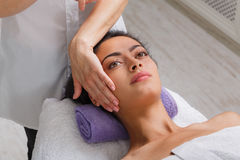 Woman massagist make face lifting massage in spa wellness center Royalty Free Stock Photos