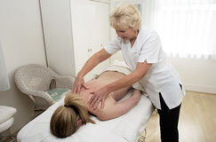 Woman and masseuse giving massage Royalty Free Stock Images